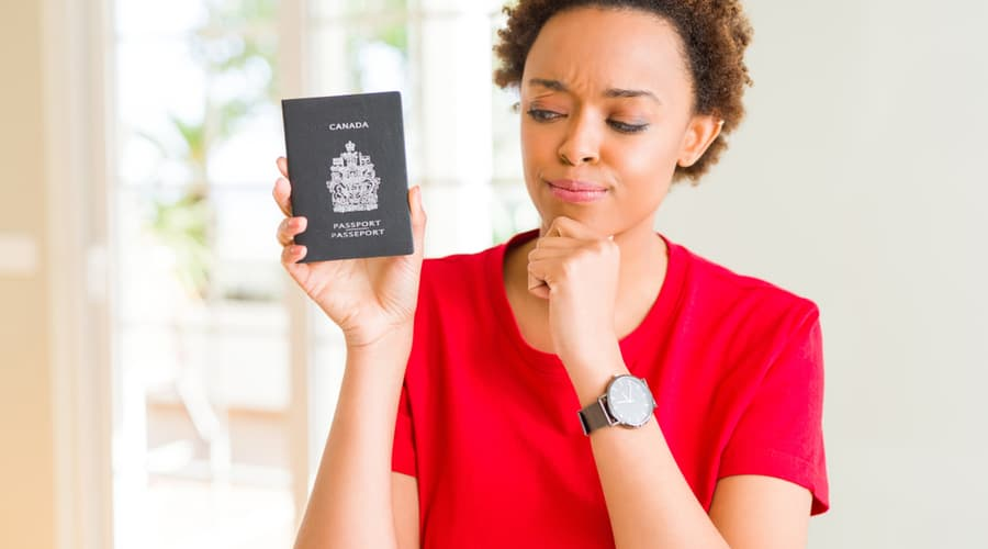 Woman holding Canadian passport while thinking