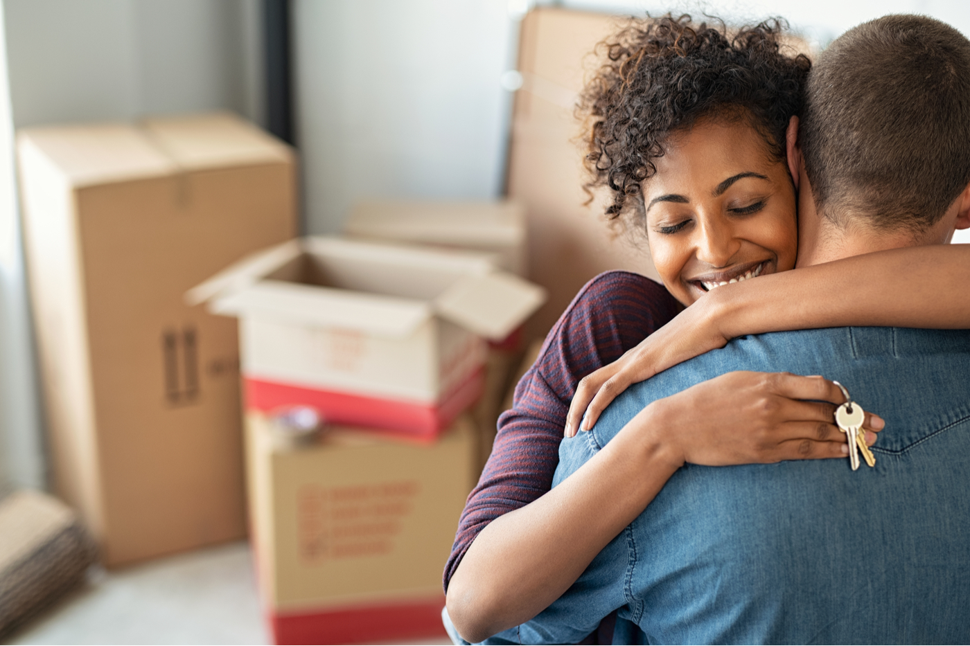 Woman hugging her husband while holding house keys