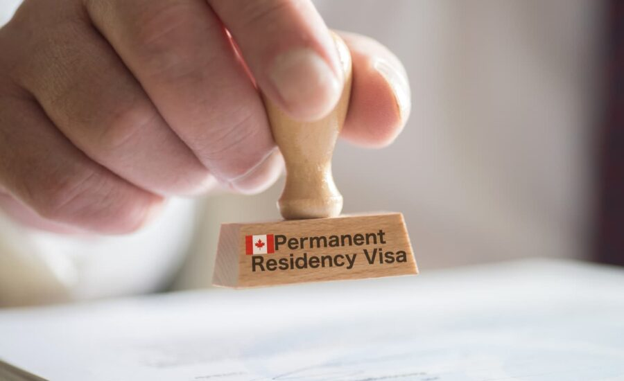 Man holding Canadian permanent residency stamp