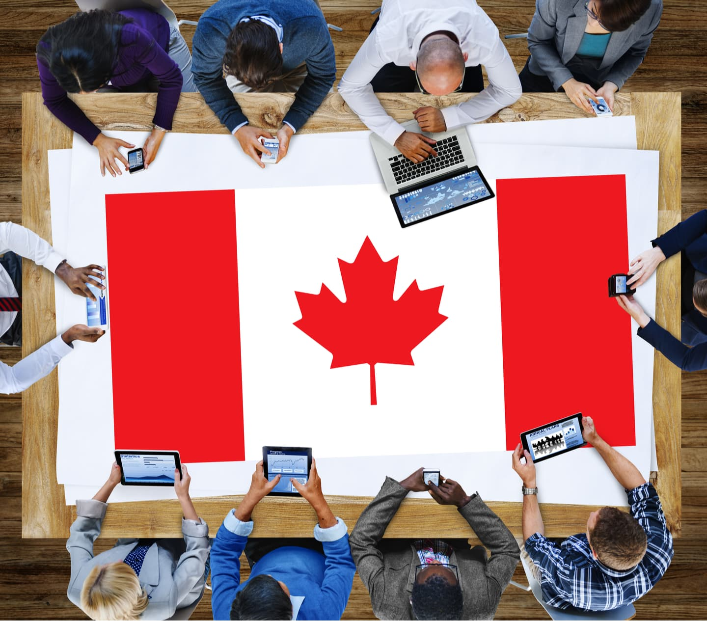 People working together with Canadian flag on the table