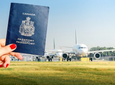 Woman holding Canadian passport on airport background